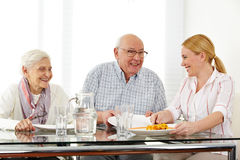Family with senior couple eating Royalty Free Stock Image