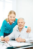Family with senior man solving crossword puzzle Royalty Free Stock Photo