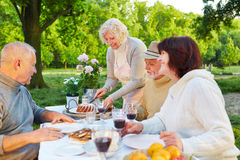 Family with senior people eating cake at birthday party. In a garden Royalty Free Stock Photo