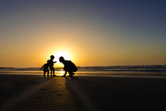 Family shadowgraph. Shadowgraphs of woman and to babies on a sunset on the beach Stock Photo