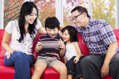 Family sharing digital tablet for play. Portrait of cheerful family sharing digital tablet for play game on sofa with autumn background Royalty Free Stock Photo
