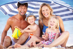 Free Family Sheltering From Sun Under Beach Umbrella Stock Photography - 27202172