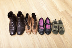 Family shoes placed in a row on hardwood floor Royalty Free Stock Photos