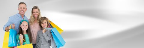 Family with shopping bags against blurry grey abstract background Stock Photography