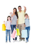 Family with shopping bags gesturing thumbs up. Portrait of happy family with shopping bags gesturing thumbs up over white background Royalty Free Stock Photography