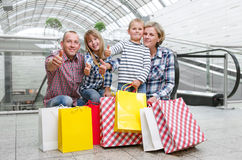 Family with shopping bags in the shopping center. Showing thumbs up Stock Photos