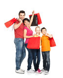 Family with shopping bags standing at studio. Happy family with shopping bags standing at studio over white background stock photo