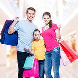 Family with shopping bags standing at studio. Happy family with shopping bags standing at studio over white background royalty free stock photo