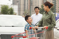 Family with shopping cart, child looking up at smiling, going shopping Royalty Free Stock Photos