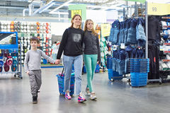 Family with shopping cart in sport goods store. Family with a shopping cart in a sport goods store Stock Images