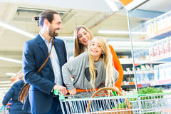 Family with shopping cart in supermarket Stock Images