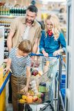 family with shopping cart waiting at cash point stock photos