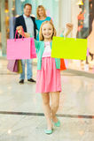 Family shopping. Cheerful family shopping in shopping mall while little girl showing her shopping bags and smiling stock image