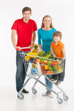 Family shopping. Cheerful family standing near shopping cart and smiling while isolated on white royalty free stock photos