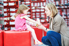 Family shopping choosing child footwear shoes. Family shoe shopping. Young women mother with little child girl daughter choosing footwear stock image