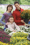 Family shopping for flowers in garden centre, man holding pot plant, smiling, portrait Royalty Free Stock Photography