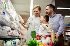 Family Shopping For Groceries. Portrait of happy family shopping in grocery store: choosing milk in dairy product department and putting it to cart royalty free stock photos