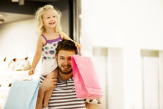 Family shopping. Happy family in shopping mall. Daughter is enjoying on father's shoulders royalty free stock photo
