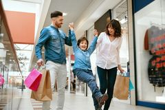 Family Shopping. Happy People In Mall. Family Shopping. Happy People With Child Carrying Bags, Walking In Modern Mall. High Resolution royalty free stock images