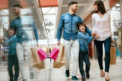 Family Shopping. Happy People In Mall. Family Shopping. Happy People With Child Carrying Bags, Walking In Modern Mall. High Resolution royalty free stock photo