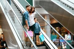 Family Shopping. Happy People In Mall. Family Shopping. Happy People With Child Carrying Bags Standing On Escalator Stairs In Modern Mall. High Resolution Stock Images