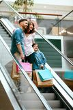 Family Shopping. Happy People In Mall. Family Shopping. Happy People With Child Carrying Bags Standing On Escalator Stairs In Modern Mall. High Resolution royalty free stock image