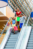 Family in shopping mall on escalators Stock Photo