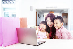 Family shopping online. Happy asian family shopping online by using laptop computer, shot at home Stock Photography