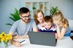 Family shopping online. Happy family shopping online with a credit card royalty free stock image