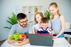 Family shopping online. Happy family shopping online with a credit card royalty free stock photo