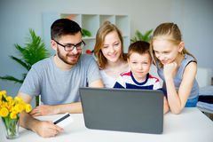 Family shopping online. Happy family shopping online with a credit card stock images