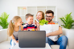 Family shopping online. Happy family of four shopping online with a laptop Royalty Free Stock Image