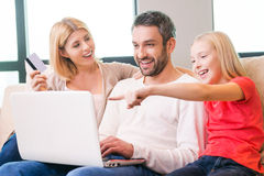 Family shopping online. Happy family of three bonding to each other and smiling while sitting on the couch and shopping online together stock images