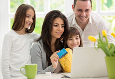 Family shopping online. Two twins girls  wit father and mother enjoying in shopping Stock Photo