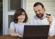 Family shopping online via the terrace on a summer evening. Family shopping online in the terrace on a summer evening Royalty Free Stock Images