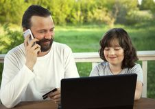 Family shopping online via the terrace on a summer evening Royalty Free Stock Photos