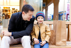 Family shopping. Family of two sitting at the bench at shopping plaza stock photography