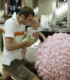 Family shopping. Young father and his daughter in the mall. He shows a huge floral bouquet Royalty Free Stock Photo