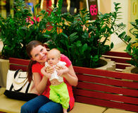 Family shopping. Young mother and her daughter on the bench. Royalty Free Stock Images