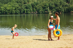 Family on the shore with a frisbee and a ball Royalty Free Stock Photo