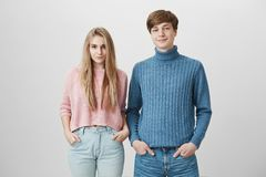 Family shot of caucasian brother and sister standing close to each other posing indoors in colourful knitted sweaters. Positive blue-eyed stylish young couple Stock Photo