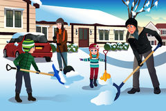 Family shoveling snow in front of their house Royalty Free Stock Photo