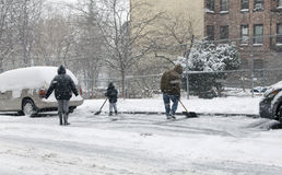 Family shoveling during snow storm in New York Royalty Free Stock Photo