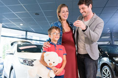Family showing key to newly bought car in showroom. Of auto dealership Royalty Free Stock Photos