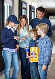 Family Showing Movie Tickets To Worker On Royalty Free Stock Photography