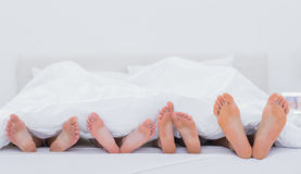 Family showing their feet. While lying on bed stock photography