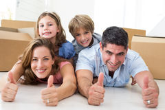 Family showing thumbs up in new house Royalty Free Stock Image