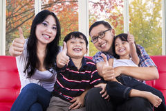 Family showing tumbs up at camera. Attractive hispanic family smiling and showing tumbs-up at camera with autumn background on the window Royalty Free Stock Photography