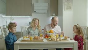 Family with siblings enjoying breakfast in kitchen stock video