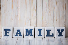 FAMILY sign made of wooden blocks on wooden background Stock Photos